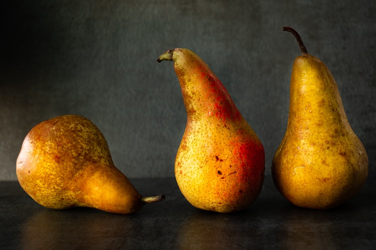 three golden pears on a table